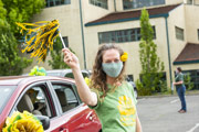 Lady with a mask on waving a green and gold flag