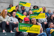 Students sitting on bleachers with HSU lumberjacks signs