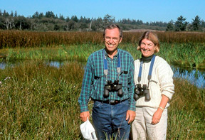 photo of Don Tuttle and his wife Andrea in from of a marsh land area