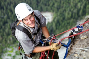 Greg Stock climbing a rock with harness