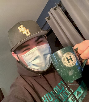 Student wearing a mask, a Green & Gold hat and sweatshirt, and holding an HSU mug.