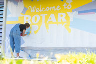 Student in overalls painting a blue and yellow mural with the words welcome to rotary park