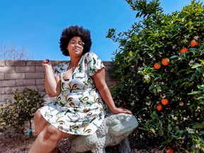 Photo of Sabina sitting on a frog stone statue next to an orange tree