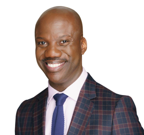 Photo of Shaun Harper in a dark plaid suit with a blue tie and white shirt