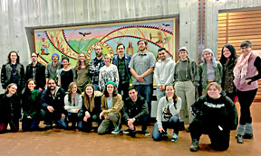 group of people standing in front a mural
