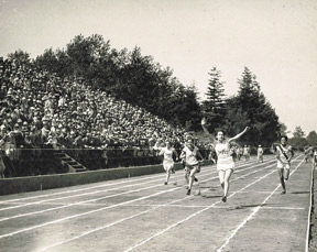 Historical black and white photo of the track and students running with their hands up