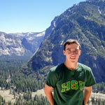 Brodie in a green HSU shirt standing in front of some large mountains