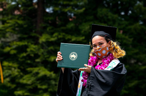 Student with a face mask wearing a graduation cap and gown holding a diploma