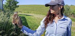 photo of Amy holding a bird out in the field