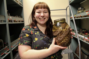 a student holding a jar from the herpetology collection